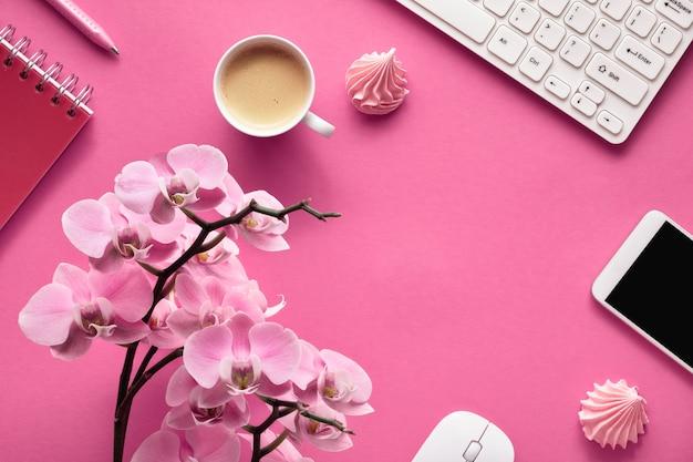 축하 계획 : 분홍색 종이에 난초와 휴대 전화, 키보드, 커피 및 invitaiton 카드
