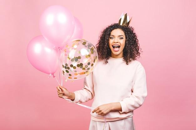 お祝いの女王のコンセプト-カラフルなパーティー風船とピンクのtシャツで幸せな陽気な若い美しいアフリカ系アメリカ人女性の肖像画を閉じます。ピンクのスタジオの背景に対して隔離。