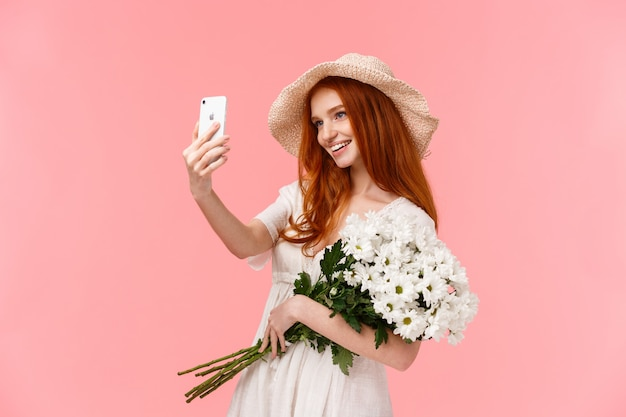 Celebration, social media and internet concept. alluring sassy redhead female in straw hat, spring dress, holding bouquet, taking selfie on smartphone with white flowers, smiling pleased