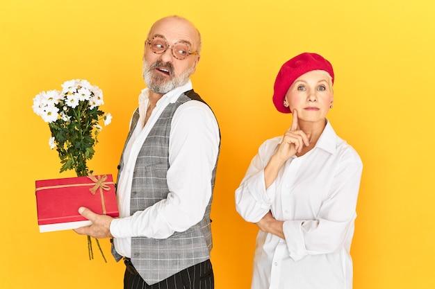 お祝い、特別な機会、ロマンスのコンセプト。感情的な面白いハクトウワシの無精ひげを生やした男性年金受給者が女性に予期しない贈り物をするつもりです。結婚記念日を祝う成熟した妻と夫