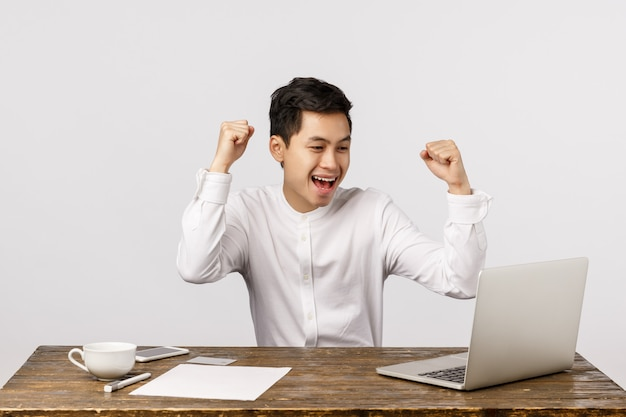 Celebration, success and finance concept. cheerful young asian man rejoicing, raising clenched fists in hooray, yes gesture, sitting desk, looking laptop screen