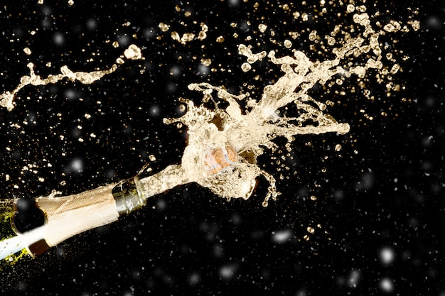 Celebration theme with splashing champagne on black background with snow