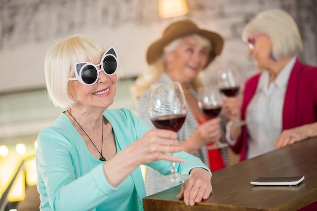 축하. 손에 와인 잔을 가진 세 수석 금발 숙녀