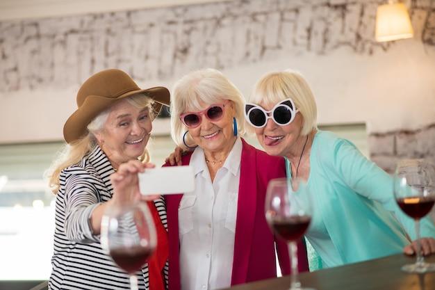 축하. 좋은 시간을 보내고 와인을 마시는 세 수석 행복한 여성