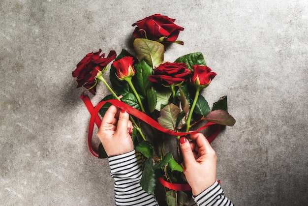 Celebratory background, valentine's day. the girl (hands in the picture) makes a bouquet of red roses, tie with a red ribbon.
