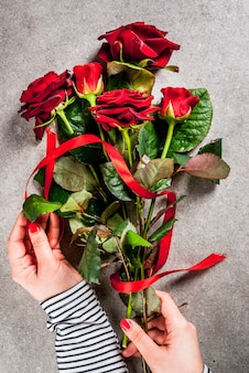 Celebratory background, valentine's day. the girl (hands in the picture) makes a bouquet of red roses, tie with a red ribbon