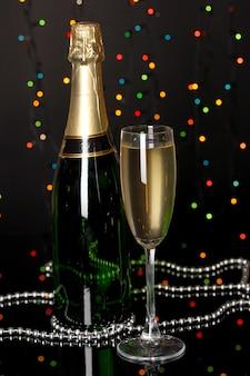 Праздничное шампанское с бокалом на фоне рождественских огней