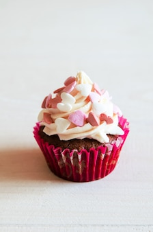 Celebratory cupcake for valentines day and happy birthday on wooden white table with hearts. give love on a holiday