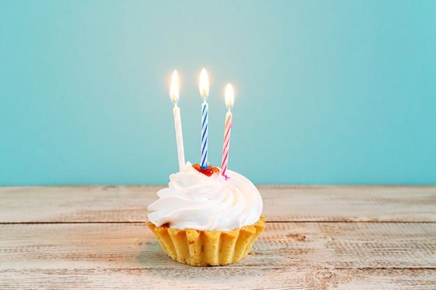 青い背景にキャンドルとお祝いのカップケーキ。誕生日や休日の装飾。