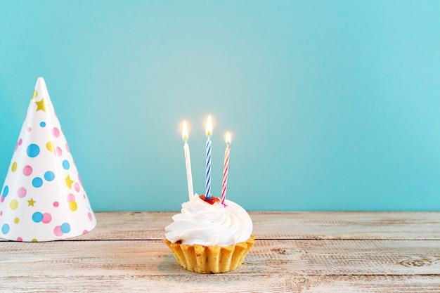 파란색 배경에 촛불과 함께 기념 컵 케 익입니다. 생일이나 휴일을 위한 장식.