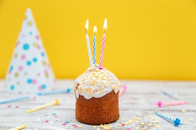노란색 배경에 촛불이 있는 기념 컵케이크. 생일이나 휴일을 위한 장식. 선택적 초점입니다.