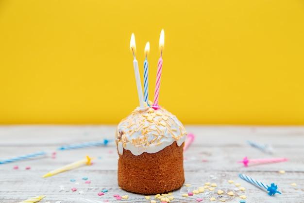 노란색 배경에 촛불이 있는 기념 컵케이크. 생일이나 휴일을 위한 장식.