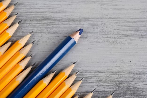 Праздничный карандаш среди обычных карандашей, на цветном фоне