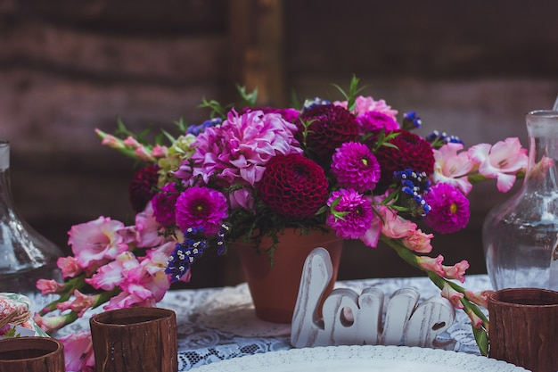 Праздничный стол украшен композициями из цветов. оригинальное свадебное цветочное украшение на свадебный стол