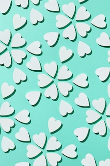 Celebratory valentine's card with creative flowers pattern handmade from plaster small hearts on a pastel turquoise wall with hard shadows, copy space. flat lay.