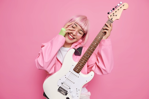 Celebrities concept. positive stylish female guitarist tilts head smiles happily keeps hand on face performs rock music on white acoustic guitar