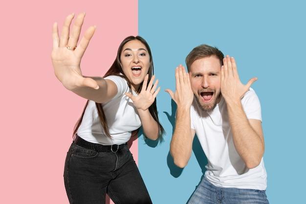Знаменитости. танцы, движения, веселье. молодой, счастливый мужчина и женщина в повседневной одежде на розовой, синей двухцветной стене. понятие человеческих эмоций, мимики, отношений, рекламы. прекрасная пара.