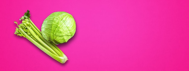 Celery branch bunch and green cabbage isolated on pink banner background. top view