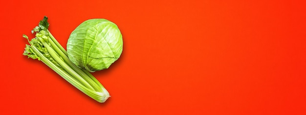 Celery branch bunch and green cabbage isolated on red banner background. top view