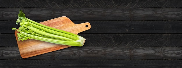 Celery branch bunch on a wooden cutting board. isolated on black wood banner background Premium Photo