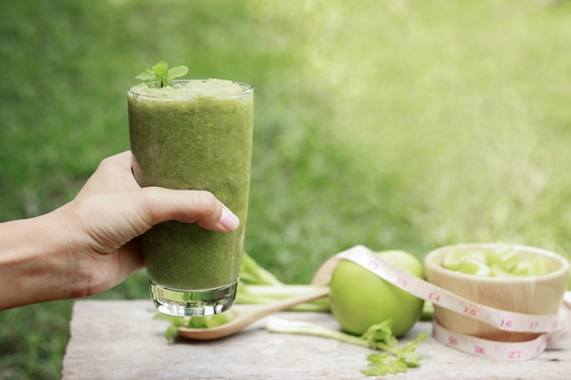 Celery juice in glass for healthy eating with fiber with hand hold