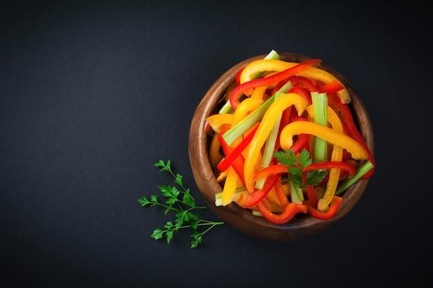 어두운 배경에 대나무 그릇에 셀러리, 빨간색과 노란색 고추 파프리카 채식 샐러드. 상위 뷰입니다. 텍스트를위한 공간. 선택적 초점.
