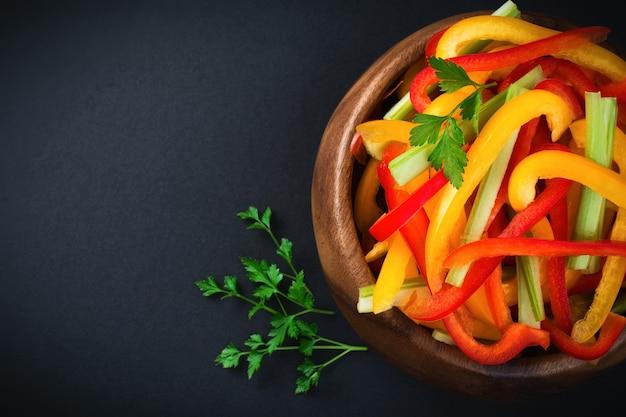 대나무 그릇에 셀러리, 빨간색과 노란색 고추 파프리카 채식 샐러드