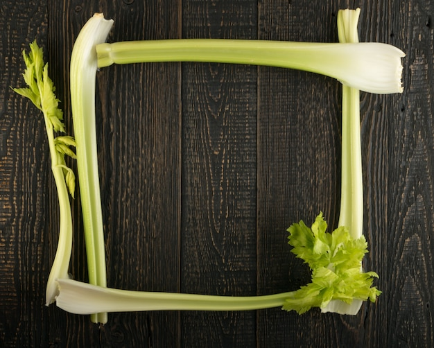 Celery stalks on wooden background