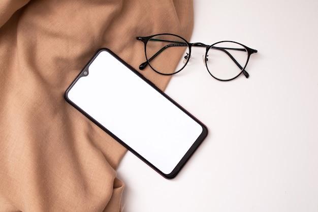 白い背景の上の携帯電話と布