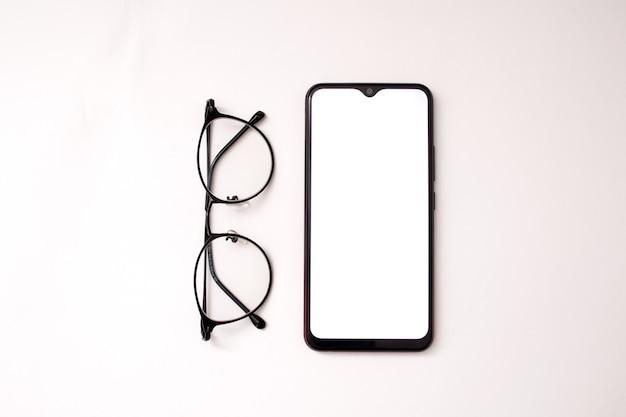白い背景の上の携帯電話とメガネ