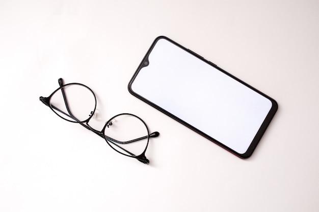 흰색 바탕에 휴대폰과 안경