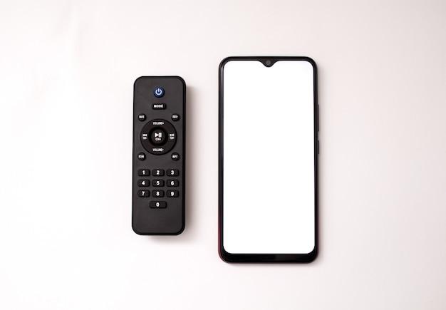 白い背景の上の携帯電話とリモコン