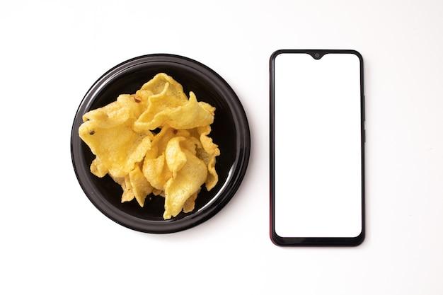 白い背景の上の携帯電話と軽食