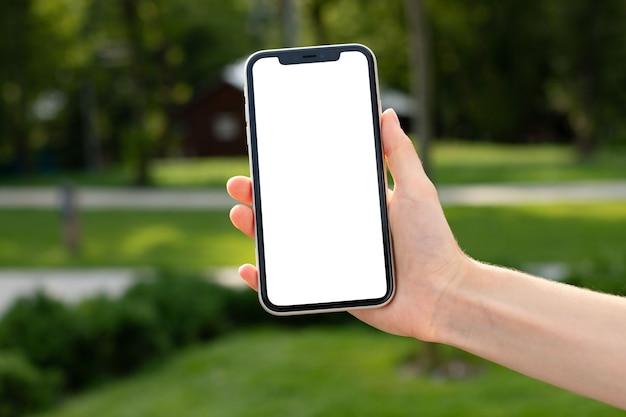Макет пустой белый экран сотового телефона. женщины рука мобильный в парке на зеленом размытом фоне. фон пустое пространство для рекламы. удаленная работа люди, контакты, маркетинг, технологии