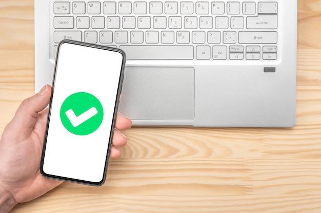 Подтверждение сотового телефона. смартфон с зеленой галочкой на экране, подтвержден, подтвержден, завершен, утвержден. подтвержденный успешный заказ смартфона. телефон в руке с подтверждением зеленой галочки