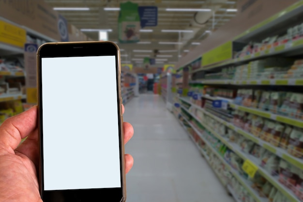 スーパーマーケットの通路のぼやけた背景を持つ手に携帯電話。