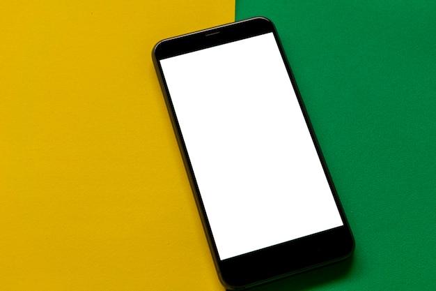 緑と黄色の背景に白い画面と携帯電話