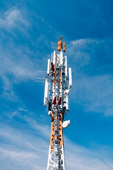 Cell tower against the surface of blue sky close up Premium Photo