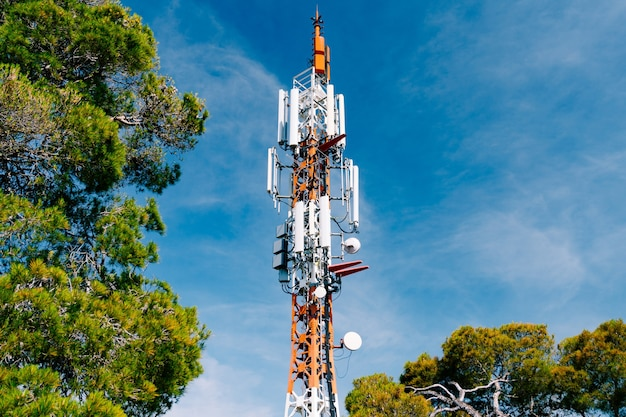Cell tower against the surface of green trees and blue sky close up