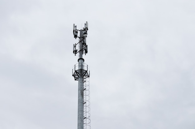 Cell tower on background of gray sky.