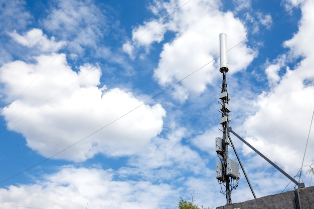 Cell tower on cloudy blue sky background