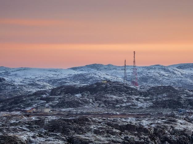Сотовые вышки на заснеженных холмах в тундре. красивый закат холмистый пейзаж арктики. кольский полуостров.