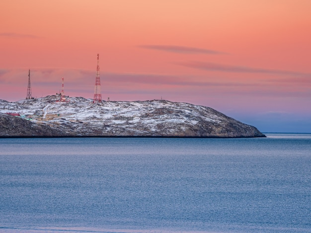 Cell towers in the snow-covered hills in tundra. beautiful sunset hilly landscape of the arctic. kola peninsula.