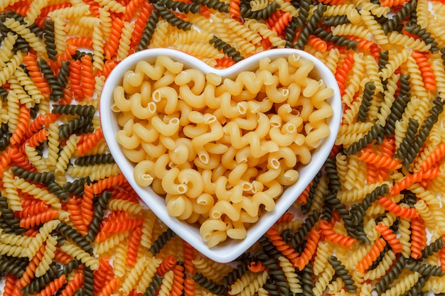 Cellentani pasta in a heart shaped plate on a colored fusilli table. top view.