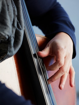 Cellist player hands. violoncellist playing cello on background of field. musical art, concept passion in music. classical music professional cello player solo perform