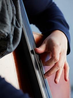 チェリスト奏者の手。フィールドの背景にチェロを弾くバイオリン奏者。音楽芸術、音楽への情熱。クラシック音楽のプロのチェロプレーヤーのソロ演奏