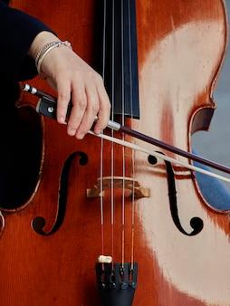 Виолончелист игрока руки. виолончелист играет на виолончели на фоне поля. музыкальное искусство, концептуальная страсть в музыке. классическая музыка профессиональный виолончелист сольное выступление
