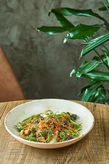 Целлофановая лапша с креветками и овощами, грибами шиитаке в белой тарелке. вок с рисовой лапшой