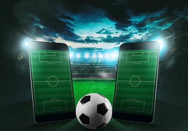 Мобильный телефон и мяч с футбольным стадионом на заднем плане