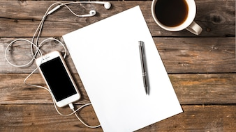 Cellphone connected with earphones; pen; paper and coffee cup on wooden background